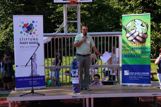 """Peter Huyeng eröffnet das Sommerfest zum Jahresmotto """"Kein Mensch flieht freiwillig - Zuhause kann überall sein"""" und präsentiert den neuen Namen und das Logo der Einrichtung"""